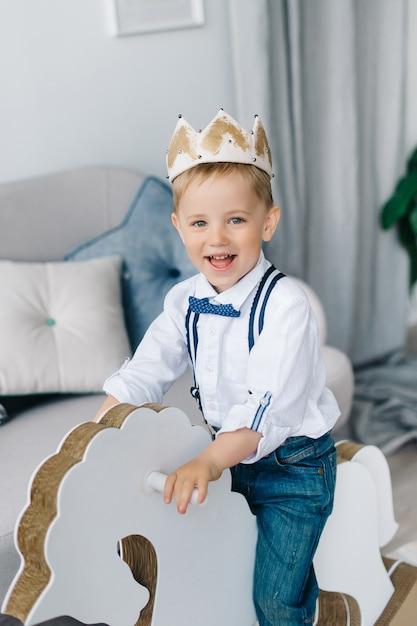 Garçon Portant Une Couronne, Un Garçon Heureux Monté Sur Un Cheval Comme Un Prince, Un Concept De Créativité Pour Rester à La Maison. Photo Premium
