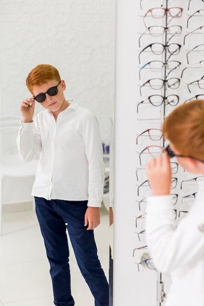 Garçon portant des lunettes noires et regardant dans le miroir au magasin d'optique Photo gratuit