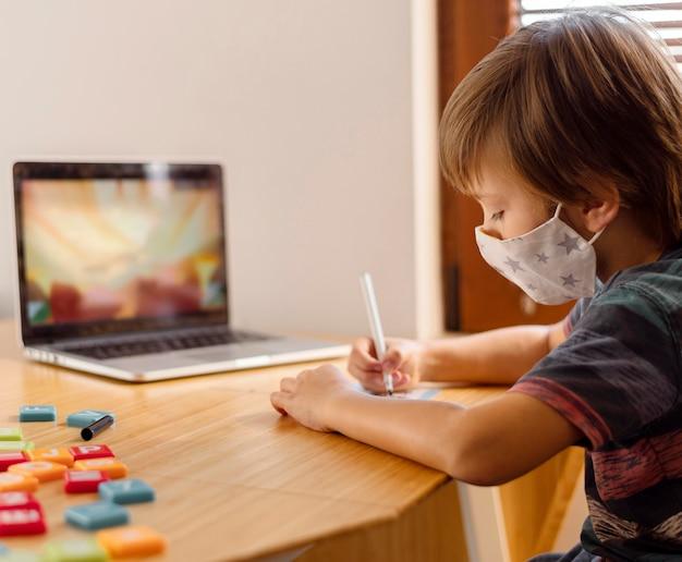 Garçon Portant Un Masque Médical Et Fréquentant Une école Virtuelle Photo gratuit
