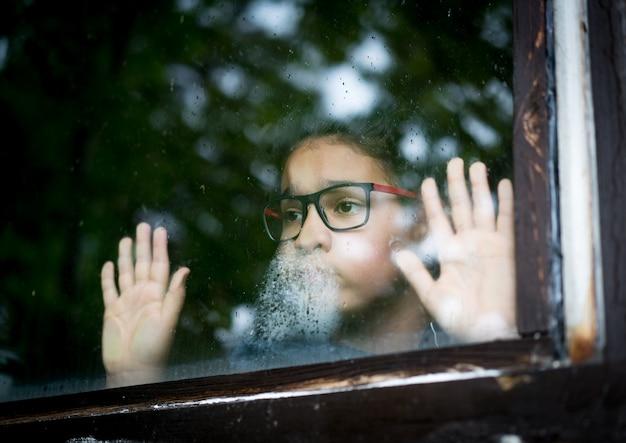 Un garçon pose sa main sur une fenêtre et regarde dehors Photo Premium