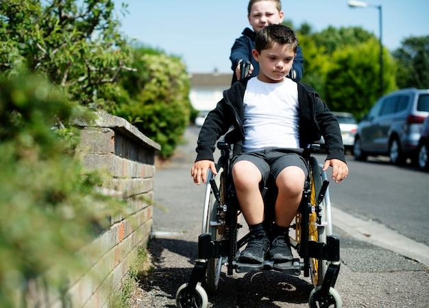 Garçon poussant son frère dans un fauteuil roulant Photo Premium
