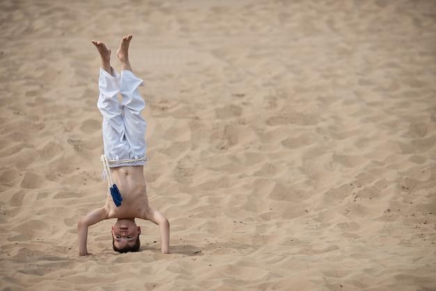 Garçon pratiquant la capoeira, le poirier Photo Premium