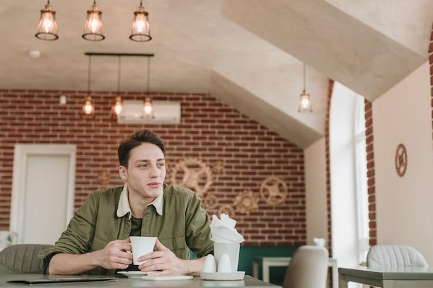 Garçon prenant un café au restaurant Photo gratuit