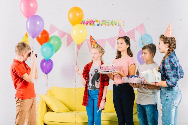 Garçon prenant une photo de ses amis avec un gâteau d'anniversaire; cadeau et ballons Photo gratuit