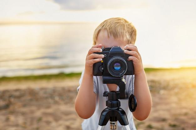 Garçon prenant des photos avec un vieil appareil photo sur la plage Photo Premium