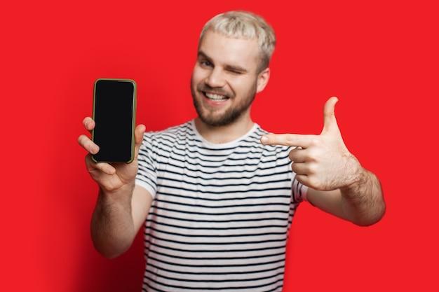 Garçon De Race Blanche Blonde Avec Une Barbe Courte Pointant Vers Le Téléphone Avec Un Espace Vide Sur Fond Rouge Photo Premium