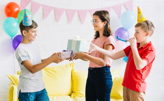 Garçon recevant un cadeau d'anniversaire de ses amis Photo gratuit