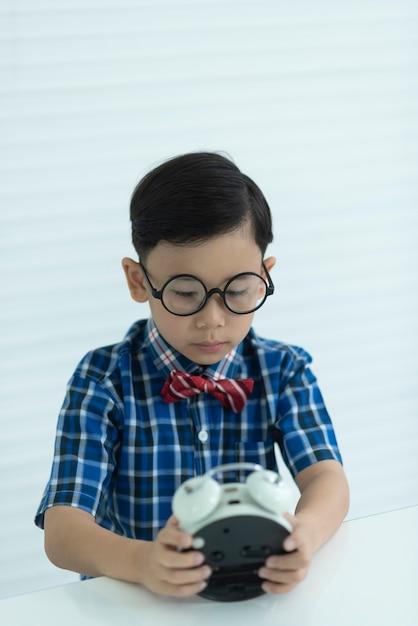 Le garçon regardait la montre de manière choquante. Photo Premium