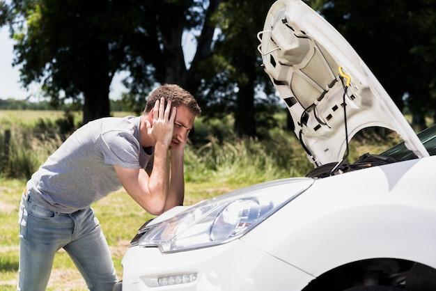 Garçon regardant une voiture en panne Photo gratuit