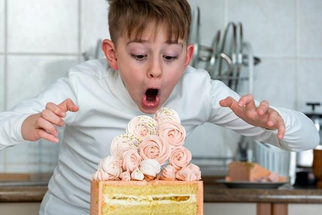 Le Garçon Regarde Le Grand Beau Gâteau Avec Surprise Et Admiration. L'enfant Veut Manger Tout Le Gâteau. Photo Premium