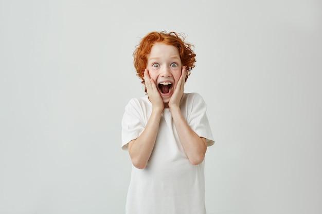 Garçon Rousse Excité Avec Des Taches De Rousseur Tenant Le Visage Avec Les Mains, Avec Une Expression Heureuse Et Une Bouche Ouverte Après Que Les Parents Lui Aient Donné Des Bonbons. Photo gratuit