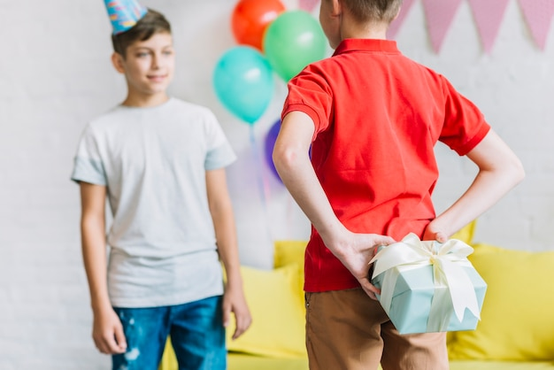 Garçon se cachant un cadeau d'anniversaire de son ami Photo gratuit