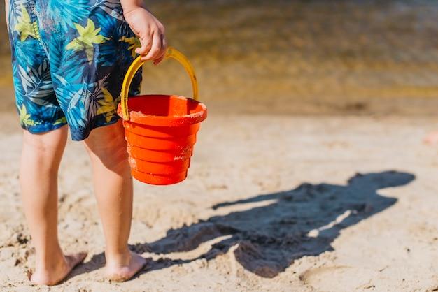 Garçon en short tenant un seau de jouet sur la plage de la mer Photo gratuit