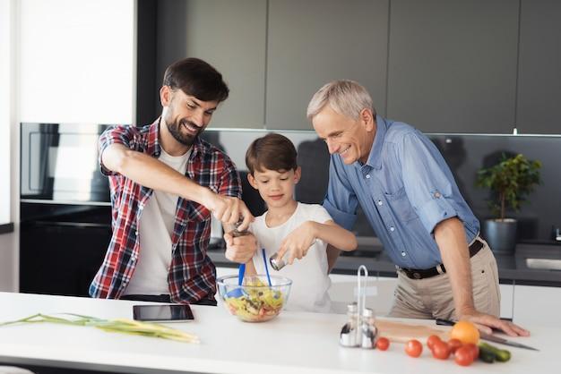 Le garçon et son père ajoutent des épices à la salade presque prête. Photo Premium