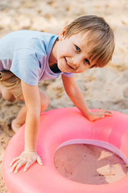 Garçon souriant avec anneau de natation sur le sable Photo gratuit