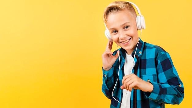 Garçon souriant avec des écouteurs et un espace de copie Photo gratuit