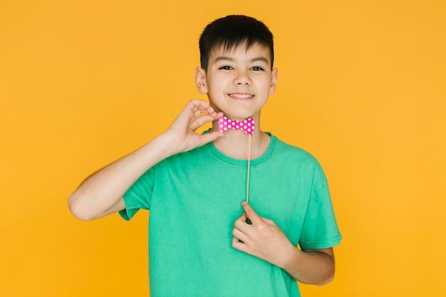 Garçon souriant essayant un faux noeud papillon Photo gratuit