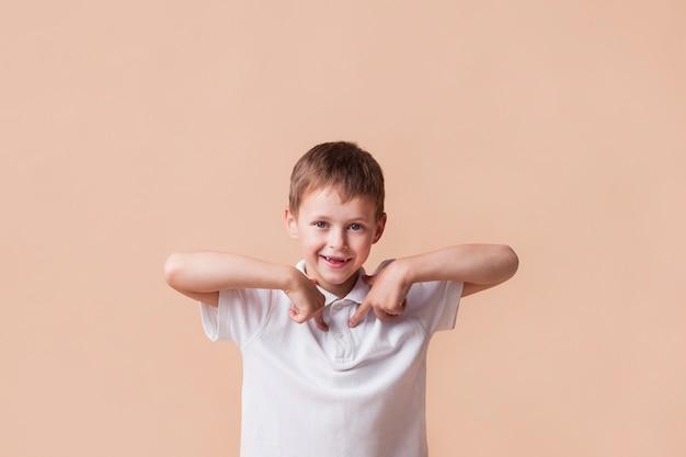 Garçon souriant, pointant l'index sur lui-même debout près du mur beige Photo gratuit