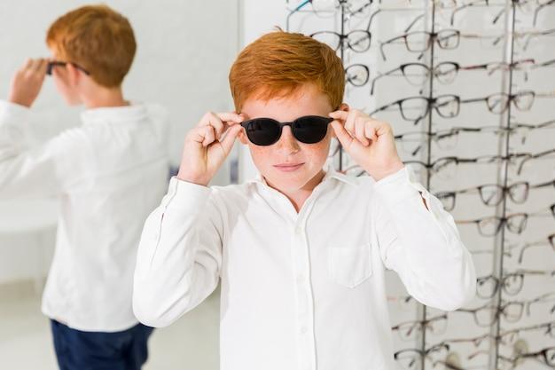 Garçon souriant portant des lunettes noires dans une clinique d'optique Photo gratuit