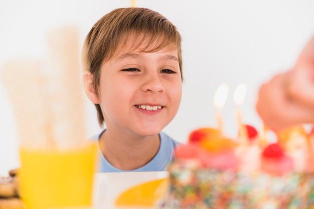 Garçon Souriant Regardant Un Délicieux Gâteau D'anniversaire Avec Des Bougies Allumées Photo gratuit
