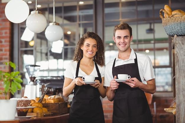Garçon souriant et serveuse tenant une tasse de café Photo Premium
