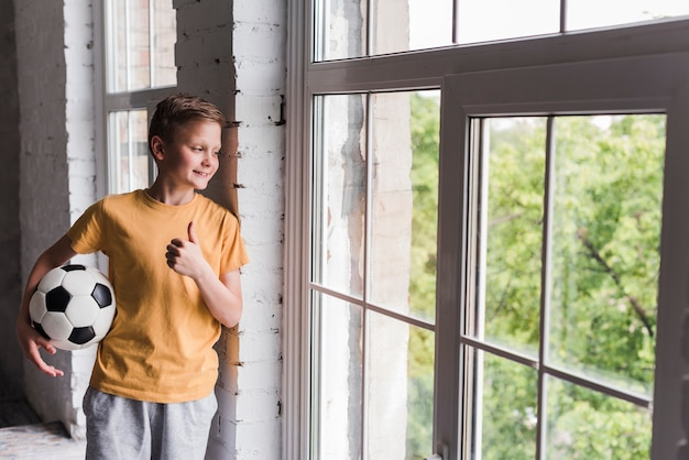 Garçon souriant tenant un ballon de foot, regardant par la fenêtre Photo gratuit