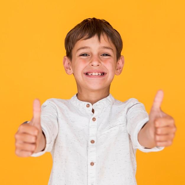 Garçon souriant vue de face donnant le signe comme Photo gratuit