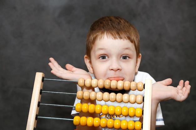 Garçon surpris étendant ses bras près du boulier en bois. Photo Premium