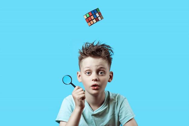 Un garçon en t-shirt léger tient une petite loupe dans sa main et un cube de rubik tombe d'en haut. Photo Premium