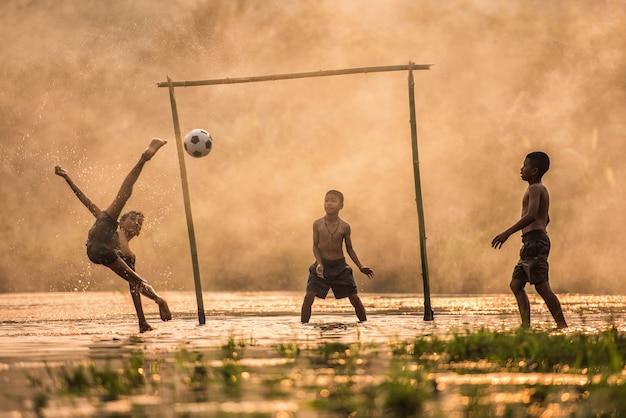 Garçon taper dans un ballon de foot Photo Premium