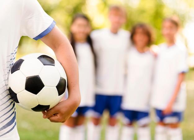 Garçon Tenant Un Ballon De Football à Côté De Ses Coéquipiers Flous Photo gratuit