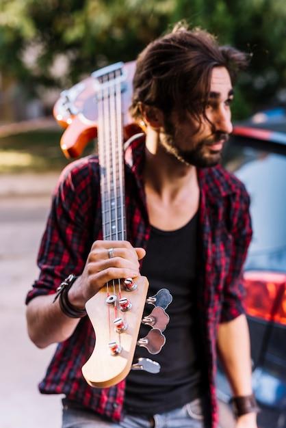 Garçon tenant la guitare électrique Photo gratuit