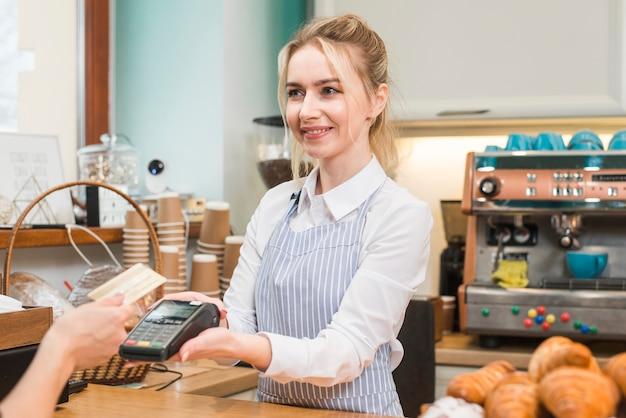 Garçon tenant une machine de balayage de carte de crédit tandis que le client montre une carte de crédit dans le café Photo gratuit