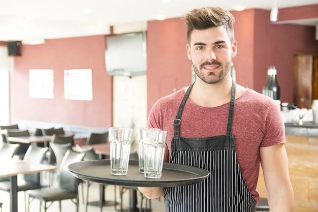 Garçon tenant un plateau avec des verres vides dans le bar Photo gratuit