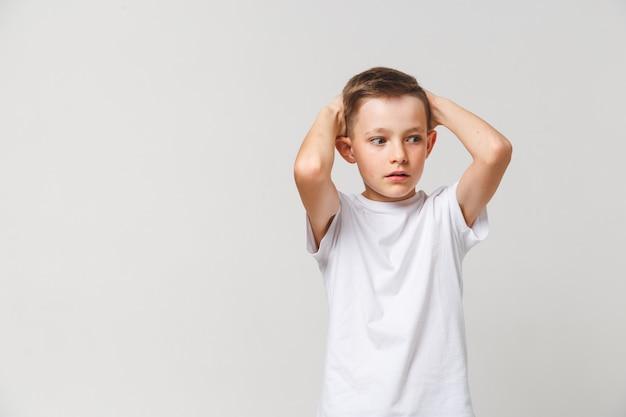 Garçon Terrifié En T-shirt Blanc Avec Les Deux Mains Sur La Tête Sur Fond Gris Photo Premium