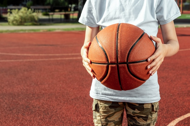 Le garçon tient dans ses mains un gros plan de basket Photo Premium