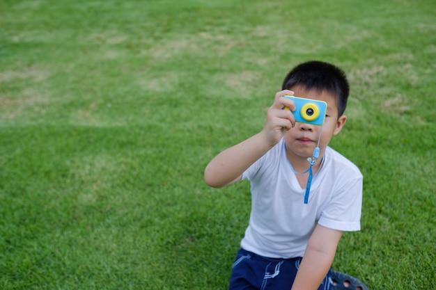 Garçon tir caméra sur herbe Photo Premium
