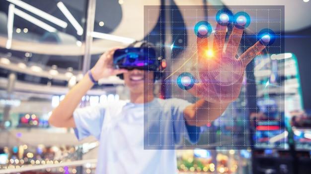Un garçon utilisant un casque de réalité virtuelle, touchez l'interface virtuelle Photo Premium