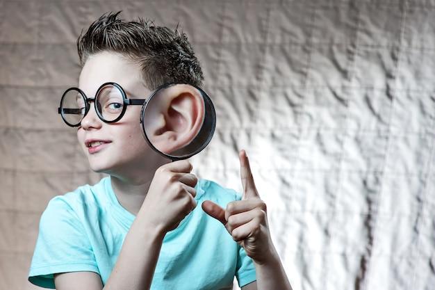 Un garçon vêtu d'un t-shirt léger penchait sa patte contre son oreille, à partir de laquelle il s'était fortement développé Photo Premium
