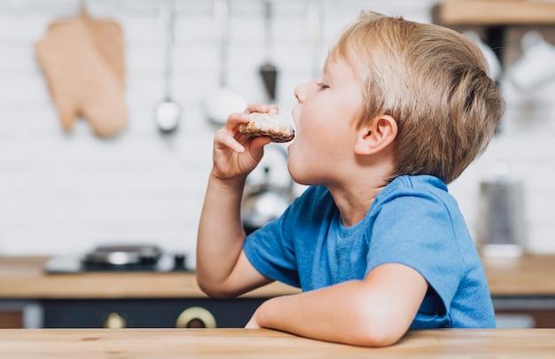 Garçon vue de côté manger un cookie Photo gratuit