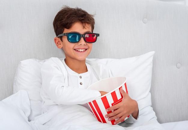Garçon vue de face avec des lunettes 3d et manger des pop-corn Photo gratuit