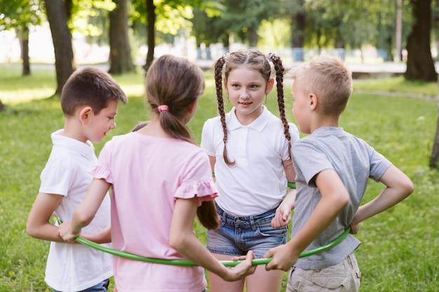Garçons et filles jouant avec cerceau Photo gratuit