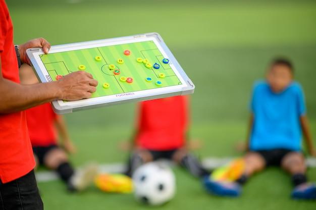 Garçons jouant au football sur le terrain d'entraînement Photo Premium