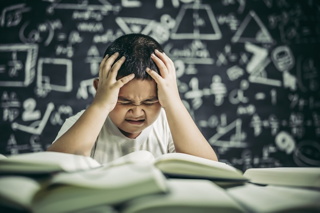 Les Garçons Avec Des Lunettes écrivent Des Livres Et Réfléchissent En Classe Photo gratuit