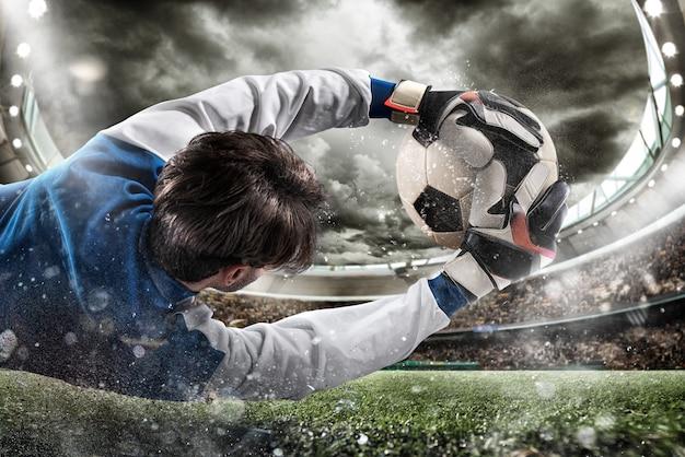 Le Gardien Attrape Le Ballon Dans Le Stade Photo Premium