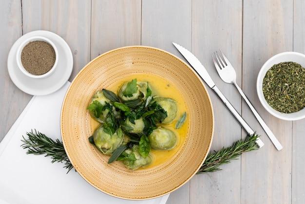 Garnir les pâtes raviolis aux herbes et épices sur une table en bois Photo gratuit