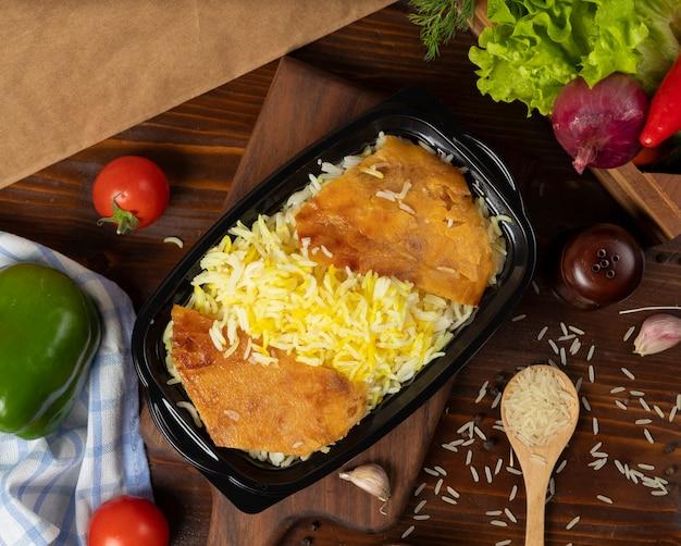 Garniture de riz, plats à emporter dans un récipient noir sur une planche en bois. Photo gratuit