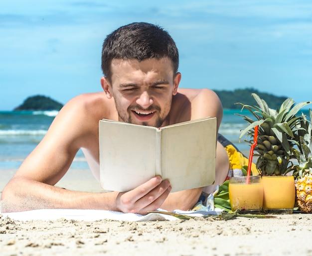 Le Gars Allongé Sur La Plage Et Lisant Un Livre Sur Le Fond De L'été Photo gratuit