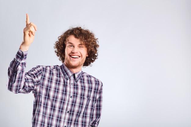 Le Gars Aux Cheveux Bouclés A Soulevé Le Gars Heureux Avec L'idée Avec Une émotion Positive Photo Premium