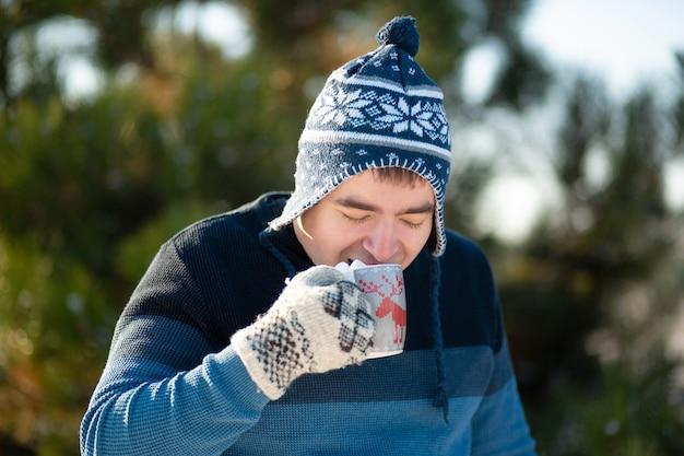 Le gars boit une boisson chaude avec des guimauves en hiver dans la forêt. une agréable promenade hivernale dans les bois avec une boisson chaude. il y a de la guimauve dans une tasse avec un verre. photo drôle Photo Premium
